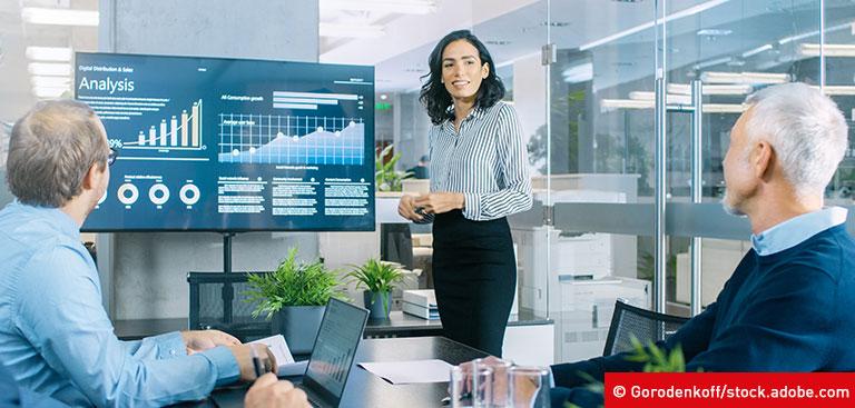 Frau präsentiert vor großem Bildschirm KPIs für den Customer Service