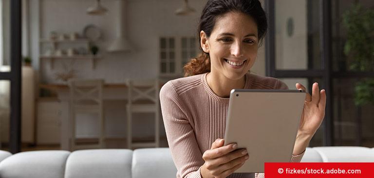 Frau sitzt auf Couch und nutzt Self-Service am Tablet